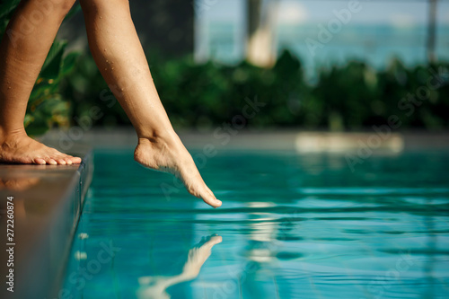 Fotografia Closeup young female leg touch blue water in swimming pool