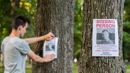 Valokuva  A young man puts up ads for a missing person in the park