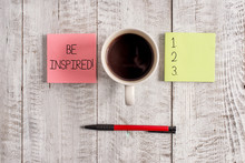 Writing Note Showing Be Inspired. Business Concept For Fill Someone With Urge Or Ability To Do Or Feel Something Stationary Placed Next To A Cup Of Black Coffee Above The Wooden Table