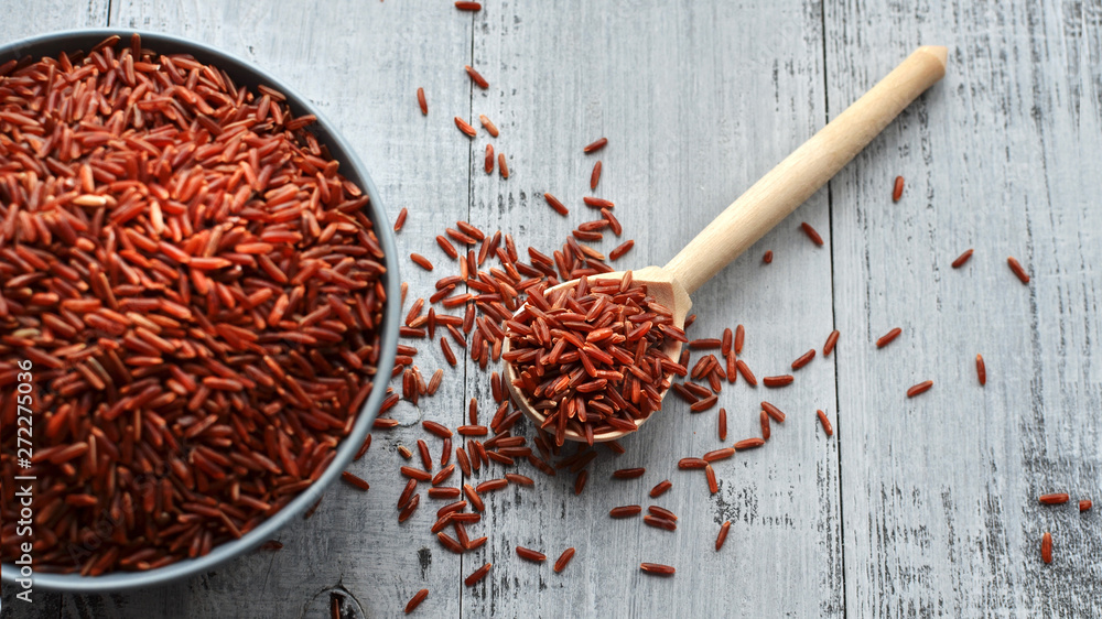 Fototapety, obrazy: Bowl and full spoon with uncooked red rice on wooden background, top view