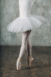 Ballerina in ballroom. Young woman ballet dancer, legs and pointe shoes and white tutu. Ballet concept.