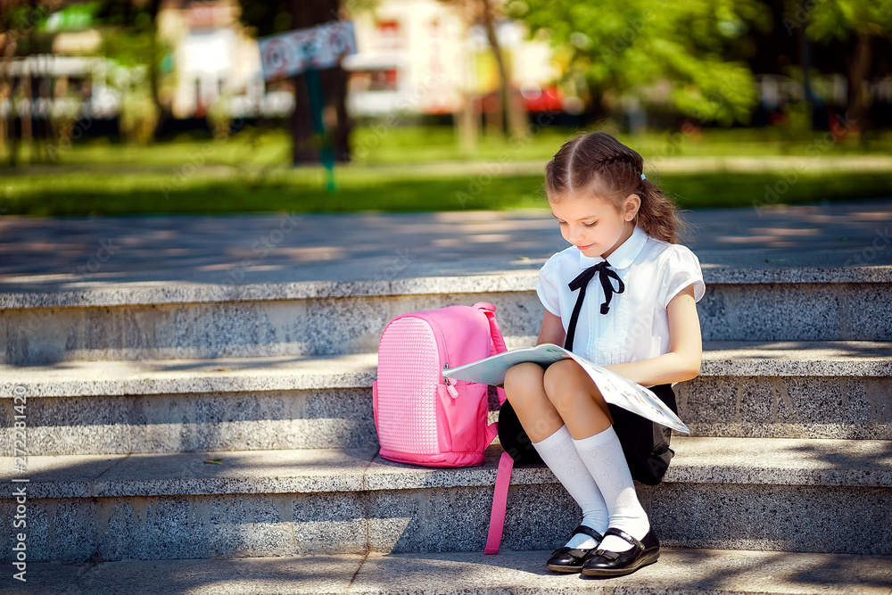 Fototapeta Pupil of primary school read book sitting on stairs. Girl with backpack near building outdoors. Beginning of lessons. First day of fall.