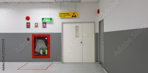 Slika na platnu Fire exit way door and fire exit sign lightbox and fire hose in electronic industry ,Green emergency exit sign door direction in case of emergency signage,Fire safety symbol and fire protection