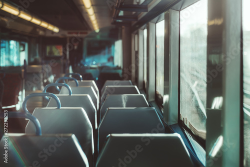 Tuinposter An interior of a modern empty ordinary suburban train in Europe with a row of double seats, shallow depth of field with selective focus, railroad tracks outside the window