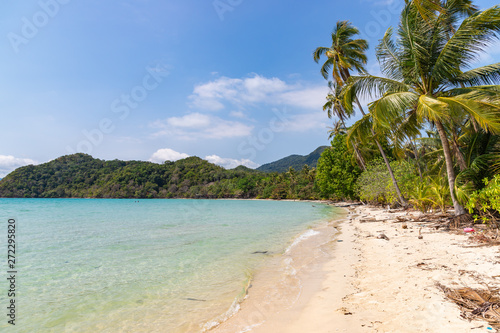 Long beach of Koh Chang island. Tropical sandy beach with palm trees and tropical forest. Thailand.
