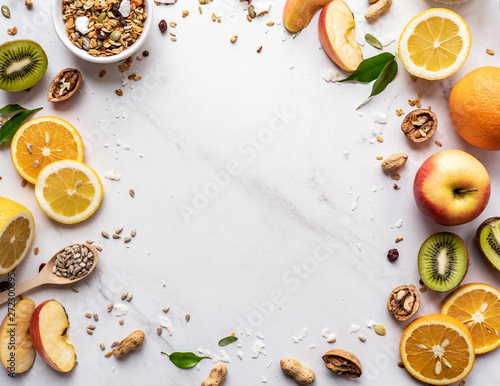 Fototapeta Healthy food vegan breakfast nutrition concept, fresh summer fruits nuts granola seeds on white background, organic super food on table, detox diet for health care, top close up view, copy space obraz