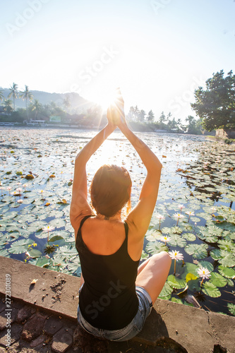 fototapeta na drzwi i meble Woman practices yoga on a lake with lotus water lilies