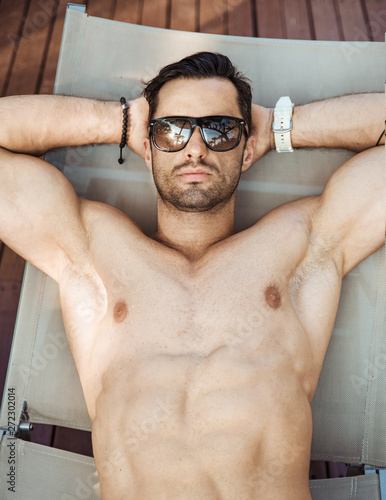 Portrait of a handsome, muscular man relaxing on a deck-chair