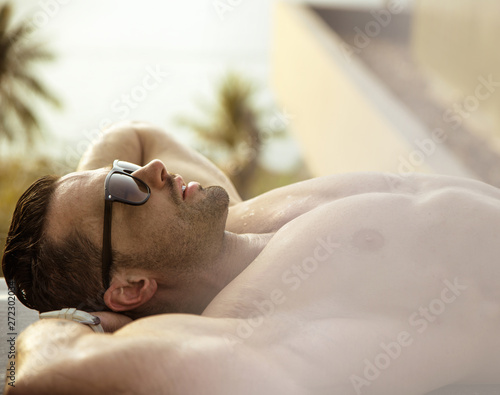 Fotobehang Artist KB Handsome, muscular man relaxing on a tropical beach
