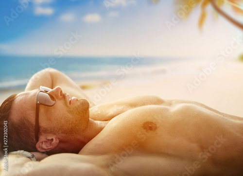 Handsome, muscular man relaxing on a tropical beach