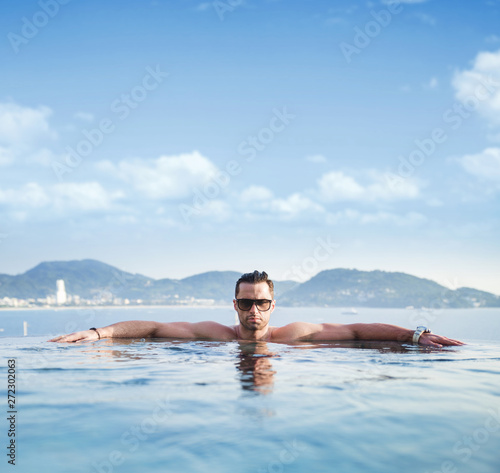 Portrait of a serious man in a tropical pool