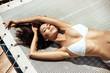 Leinwandbild Motiv Sensual young lady relaxing by the tropical pool
