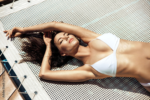 Tuinposter Artist KB Sensual young lady relaxing by the tropical pool
