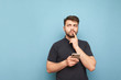 canvas print picture - Thoughtful man with a beard standing on a blue background with a smartphone in his hand, looking sideways and thinking wearing a dark t-shirt. Isolated. Copy space