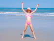 Young happy teen girl having fun on tropical beach and jumping in pink swimsuit and striped hat into the air on the sea coast at the day time. Summer travel and vacation concept