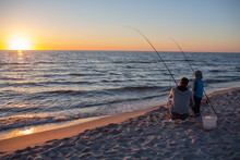 Father And Son Catch Fish On The Baltic Coast At Sunset
