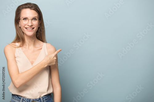 Fotomural  Happy young woman pointing on blank copy space for text.