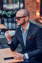 Cheerful Groomed Gentelman In Sunglasses Is Enjoying His Coffeebreak With Cup Of Fresh Latte.
