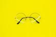 Leinwandbild Motiv Round glasses on yellow background. Fashion accessory for a clear view.