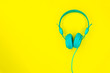 Leinwanddruck Bild - Turquoise or blue headphones or a computer headset on a yellow background with copy space.