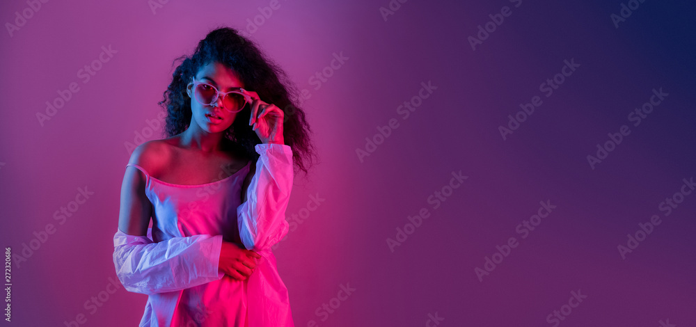 Fototapeta Fashion young african girl black woman wear stylish pink glasses clothes looking at camera isolated on party purple studio background, horizontal banner for website design, portrait, copy space