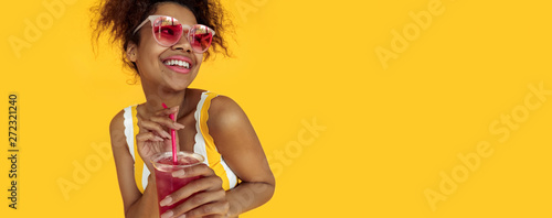 Fototapeta Happy young african woman holding drink wear glasses laughing, cheerful black teen girl enjoy summer detox cocktail having fun isolated on yellow studio background, banner website design, copy space obraz