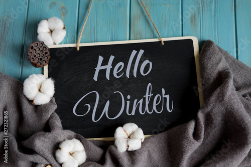 Hello winter postcard. Winter banner with warm gray shawl, cotton flowers on a blue wooden background