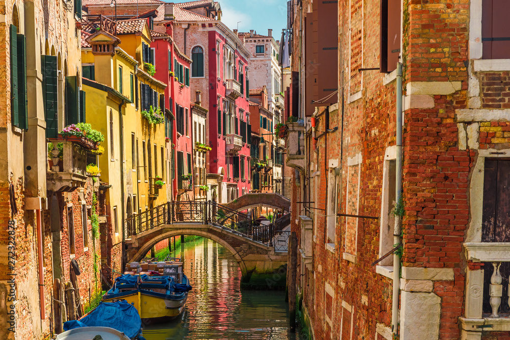 Venetian canal with boats and colorful facades of old medieval houses in Venice, Italy