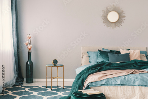 Fototapeta Flowers in stylish bottle like vase next to trendy nightstand with clock in beautiful bedroom interior with beige and emerald green bedding obraz