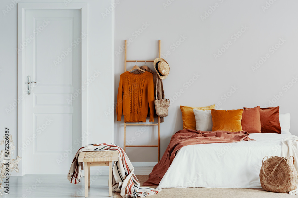 Fototapety, obrazy: Sweaters, wicker hat and bag on wooden ladder next to king size bed with velvet pillows in white bedroom interior, copy space on empty wall