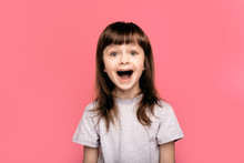 Wow. Crazy Good News. Image Of Overjoyed Excited Screaming Amazed Little Child Girl Standing Isolated Over Pink Background. Looking Camera With Open Mouth.