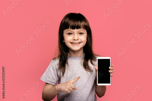 Look at this cell phone! Pleased happy little girl showing blank screen of smart sell phone, modern device, dressed in fashionable t-shirt, isolated over pink background. Technology concept