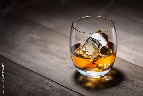 Single glass of scotch whisky, craft bourbon on ice on rustic barrel wood surface at distillery
