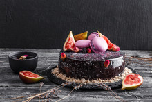 Chocolate Mousse Cake With Mirror Glaze Decorated With Macaroons, Figs, Flowers On Dark Rustic Background. Holiday Cake Celebration, Close Up