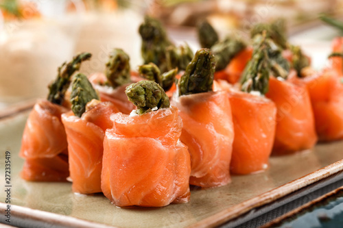 Rolls of salmon fish with cream cheese, shrimp and asparagus on banquet table Canvas Print