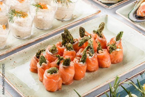 Photo  Rolls of salmon fish with cream cheese, shrimp and asparagus on banquet table