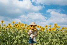 青空とひまわり畑に立つひまわりを持つ女性