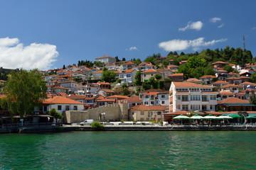 Fototapeta na wymiar Ochrid, Macedonia: toursit walking and enjoing in the view of old part of Ochrid city on a boat dock on a Ochrid lake