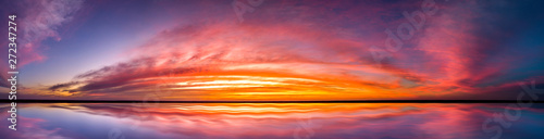 Fototapeta Panorama Reflection of vivid sunset sky over sea.Colorful sunrise with Clouds over ocean.  obraz