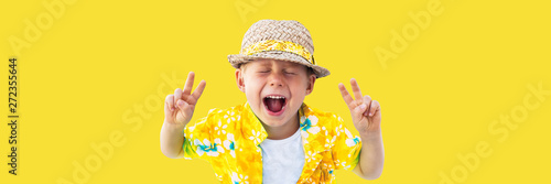 Photo  Child in yellow hawaiian shirt and straw hat shouts