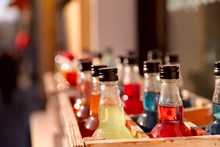 Bottles In A Wooden Box Filled With Colored Drinks. Background.Crop Shot, Close-up, Free Space For Text, Blurred. Production Concept
