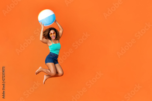 Fotografie, Obraz  Young energetic African American woman holding beach ball and jumping