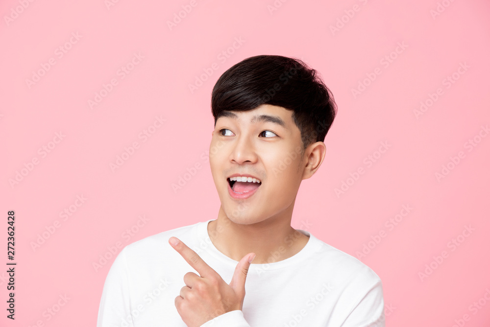 Fototapeta Young handnsome Asian man pointing hand to empty space