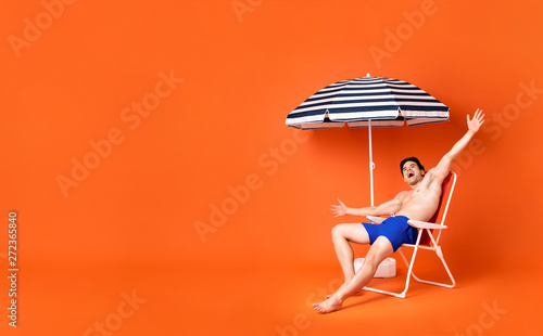 Photo sur Toile Les Textures Shirtless happy young man sitting on beach chair smiling with arms outstretched