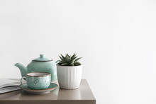 Succulent In Pot With Cup And Teapot On Table In Room
