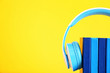 canvas print picture - Books and modern headphones on color background. Concept of audiobook