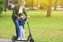 Cute Little Boy With Grandfather Riding Kick Scooter In Park