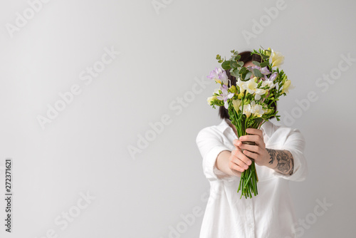 Wall Murals Floral Woman with beautiful freesia flowers on light background