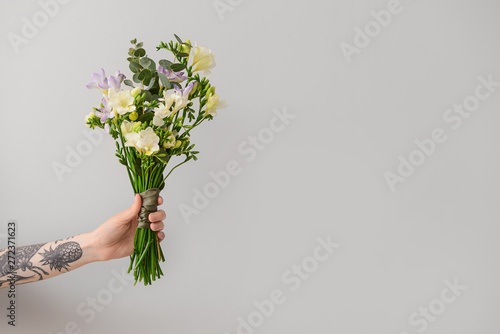 Cadres-photo bureau Fleuriste Female hand with beautiful freesia flowers on light background