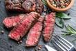 Leinwanddruck Bild Medium rare Ribeye steak with herbs on graphite board.